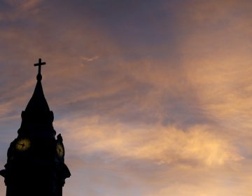 In this Sept. 27, 2015 file photo, clouds are lit by the rising sun over St. Augustine Roman Catholic Church in Philadelphia.  Pennsylvania's Roman Catholic dioceses have paid nearly $84 million to 564 victims of sexual abuse, a tally that's sure to grow substantially in 2020 as compensation fund administrators work through a backlog of claims, according to an Associated Press review.  (Julio Cortez/AP Photo)