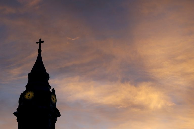 In this Sept. 27, 2015 file photo, clouds are lit by the rising sun over St. Augustine Roman Catholic Church in Philadelphia. (Julio Cortez/AP Photo)