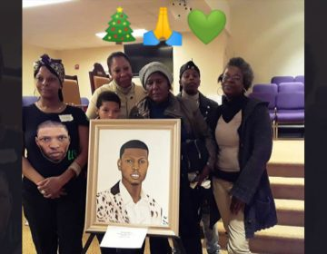 Members of Virgil's family picking up a donated portrait of him this December. (Courtesy of Sandy Ross)