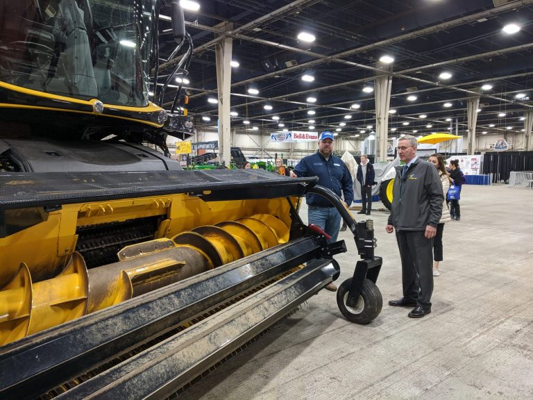 Agriculture Secretary Russell Redding (right) looks at a piece of harvesting equipment with Jason Forrester of Forrester Farm Equipment in Chambersburg, Pa. Redding was giving a tour at the Pennsylvania Farm Show Complex on Monday, December 30, 2019. (Rachel McDevitt/WITF)