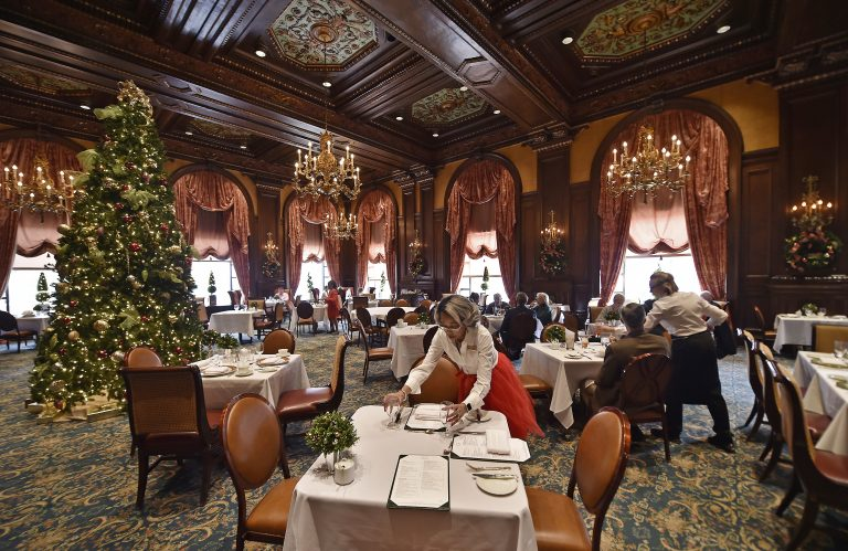 Sheila Marlowe, a hostess at the Green Room for 13 years and counting, sets up a table during lunch on Monday, Dec. 23, 2019, at the Hotel DuPont in downtown Wilmington, Delaware. (Butch Comegys for WHYY)