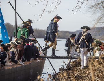 George Washington portrayed by John Godzieba steps ashore on the New Jersey side of the Delaware River. (Jonathan Wilson for WHYY)