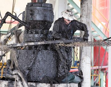 A drill worker covered in mud, shale, and drill cuttings seals off a well and cleans the blowout preventer at a Cabot Oil and Gas natural gas drill site in Kingsley, Pa.  (Lindsay Lazarski/WHYY)