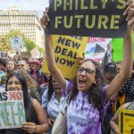 Materman High School seniors Iman Acharya and Alina Kilcullen cheer speakers at a climate strike in September (Jonathan Wilson for WHYY)