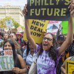 Materman High School seniors Iman Acharya and Alina Kilcullen cheer speakers at a climate strike in September (Jonathan Wilson for WHYY)