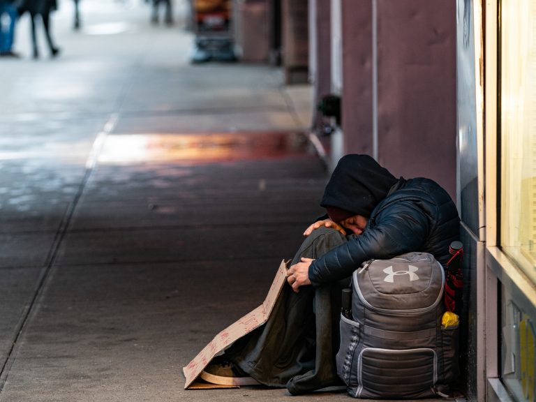 A person sleeps on a sidewalk near New York's Times Square this past week. A new report says more and more American cities are passing laws that make it illegal to sleep outside, on the street, in a park or in your own car. (Jeenah Moon/Getty Images)