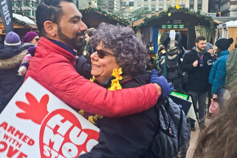 Edie Weinstein gives out hugs at the Christmas Village in Center City. (Annette John-Hall/WHYY)