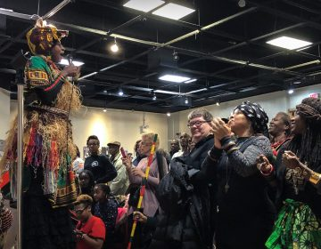 A stilt-walker leads the crowd celebrating Kwanzaa in the auditorium of the African American Museum in Philadelphia. (Michaela Winberg/Billy Penn)