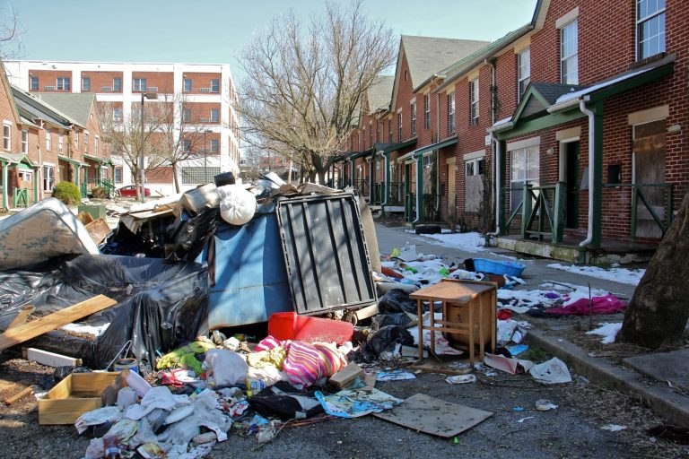 Garbage is piled in front of an apartment complex in Lower Germantown. (Emma Lee/WHYY)