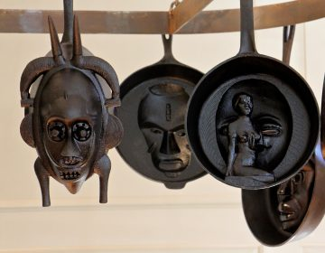 Cast iron skillets hanging in the kitchen at Bainbridge House are from Hugh Hayden's series, 'American Food.' They are modeled from African Masks and historical artifacts in the Princeton University Art Museum collections. (Emma Lee/WHYY)