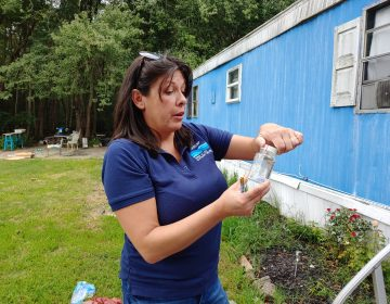 Consuelo McGowan from SERCAP collects samples for testing at a mobile home in Ellendale, Del. McGowan works for a non-profit that provides kits for testing well water. (Zoe Read/WHYY)