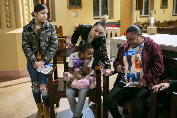 Friends and family of Sincere Howard remember his life by showing pictures at Parish of the Cathedral during a vigil in Camden, NJ on Monday, December 30, 2019. The 22 hours Vigil was held to commemorate the 24 murders in Camden City in the year 2019. (Miguel Martinez for WHYY).