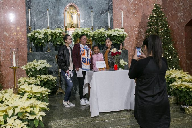 Friends and family of Sincere Howard pose for pictures in front of is his memorial at a vigil at Parish of the Cathedral in Camden, NJ on Monday, December 30, 2019. The 22 hours Vigil was held to commemorate the 24 murders in Camden City in the year 2019. (Miguel Martinez for WHYY).