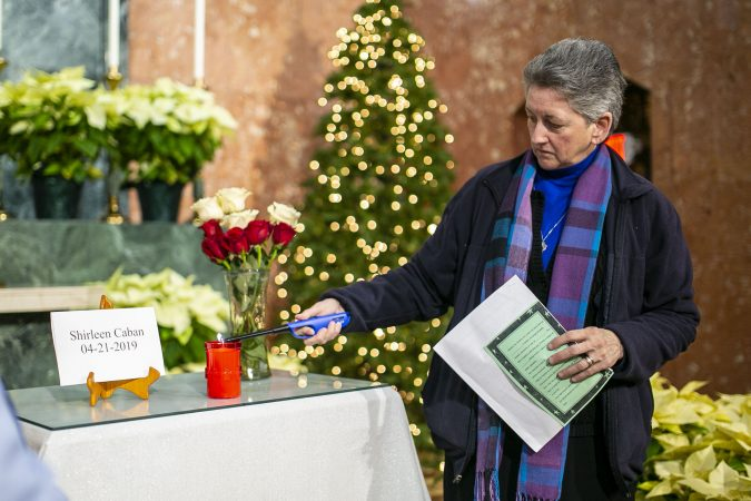 Sister Helen Cole, light up a candle for Shirleen Caban during a vigil at Parish of the Cathedral in Camden, NJ on Monday, December 30, 2019. The 22 hours Vigil was held to commemorate the 24 murders in Camden City in the year 2019. (Miguel Martinez for WHYY).
