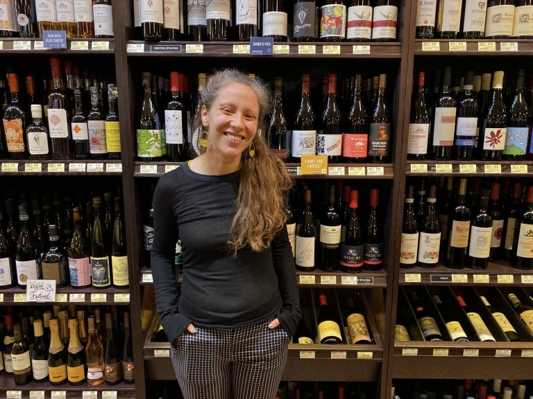 Sande Friedman, the wine buyer at Di Bruno Bros., stands in front of the stock at their Rittenhouse location. (Alex Stern/WHYY)