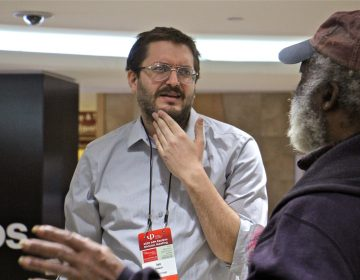 Ian Olasov (left), a part-time philosophy professor at Brooklyn College, engages with passersby at the Ask a Philosopher pop-up booth at Suburban Station in Center City. (Emma Lee/WHYY)