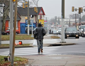 A pedestrian crosses Roosevelt Boulevard at Rising Sun Avenue. (Emma Lee/WHYY)