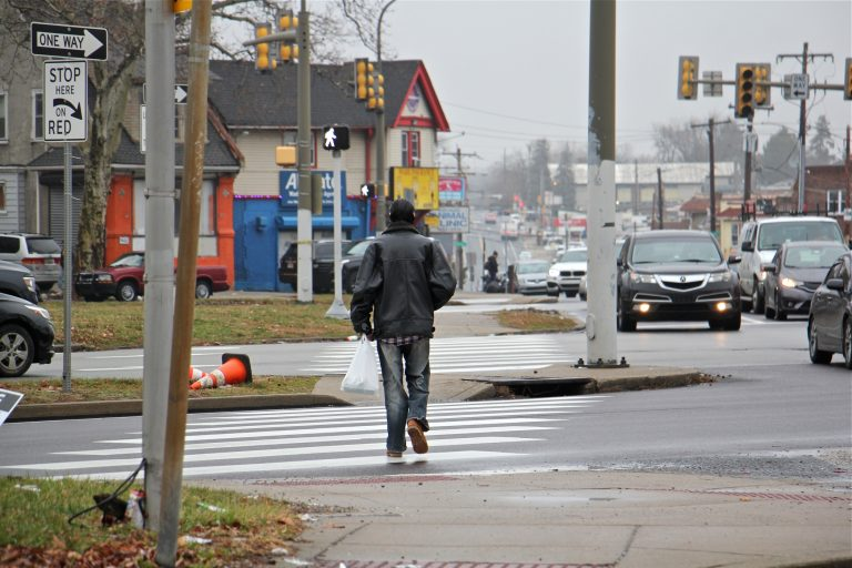 A pedestrian crosses 12 lanes of Roosevelt Boulevard at Rising Sun Avenue. (Emma Lee/WHYY)