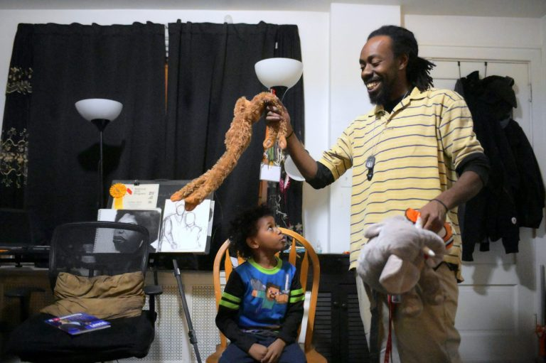 Single parent Deshaun Sherrill and his son Zay'ion Ventura-Sherrill clean up the living room of their home in West Philadelphia. (Bastiaan Slabbers for WHYY)
