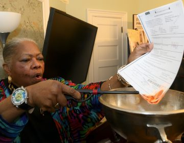Vernoca Micheals reacts as she lights the documents during the ceremonial burning of the mortgage, at the Paul Robeson House, in West Philadelphia, on Saturday. (Bastiaan Slabbers for WHYY)