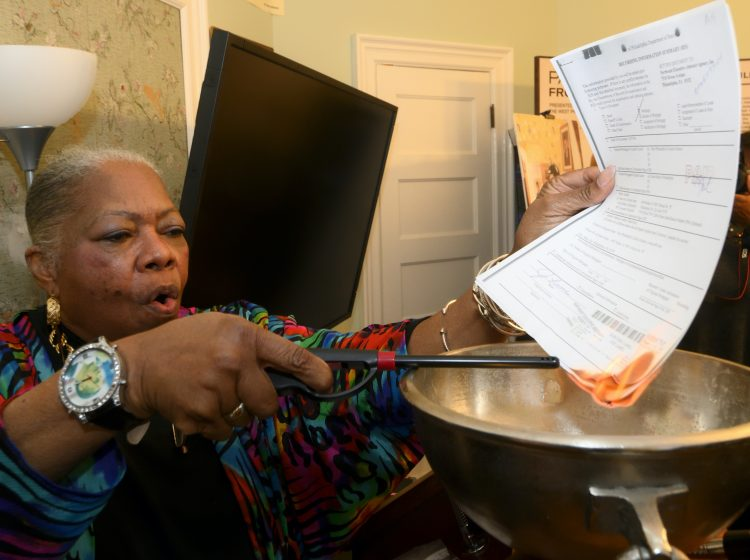 Paul Robeson House Executive Director Vernoca Micheal lights the house's mortgage during a ceremonial burning on Saturday, Jan. 25, 2020. (Bastiaan Slabbers for WHYY)
