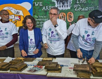 Philadelphia District Attorney Larry Krasner (center right) wields a hammer at the KingDayofService at Philadelphia's Girard College. (Kimberly Paynter/WHYY)