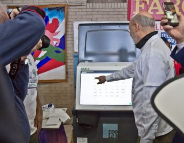 Pa. Gov. Tom Wolf poses with Pennsylvania's new voting machines at the MLK Day of Service at Philadelphia's Girard College. (Kimberly Paynter/WHYY)