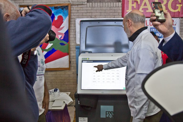 Pa. Gov. Tom Wolf poses with Pennsylvania's new voting machines at the MLKDayofService at Philadelphia's Girard College. (Kimberly Paynter/WHYY)