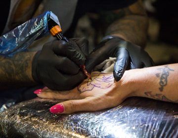 Felicia Vazquez gets a rose tattooed onto her hand by artist Ralph Fryer. (Kimberly Paynter/WHYY)