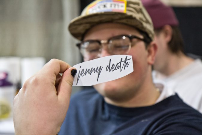 "Eric Seamans is receiving the words ""Jenny Death,"" an album title from his favorite band, the Death Grips. (Kimberly Paynter/WHYY)"