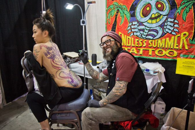 Mark Longenecker prepares to tattoo Tibetan skulls and an octopus on the back of Lindy Klensoki at the 2020 Philadelphia Tattoo Convention. (Kimberly Paynter/WHYY)