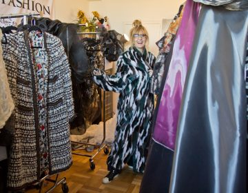 Nancy Volpe-Beringer wraps herself in an Eagles' inspired faux fur coat in her studio. (Kimberly Paynter/WHYY)