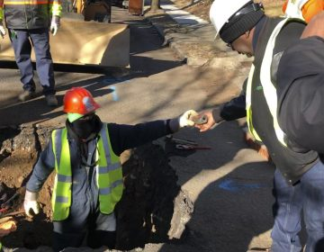 A worker hands a piece of lead pipe to a colleague as they work to remove water service lines Thursday, Jan. 9, 2020, in Trenton, N.J. The city announced it is replacing 37,000 lead pipes over five years as part of an an effort to remove the potentially harmful pipes. (Mike Catalini/AP Photo)