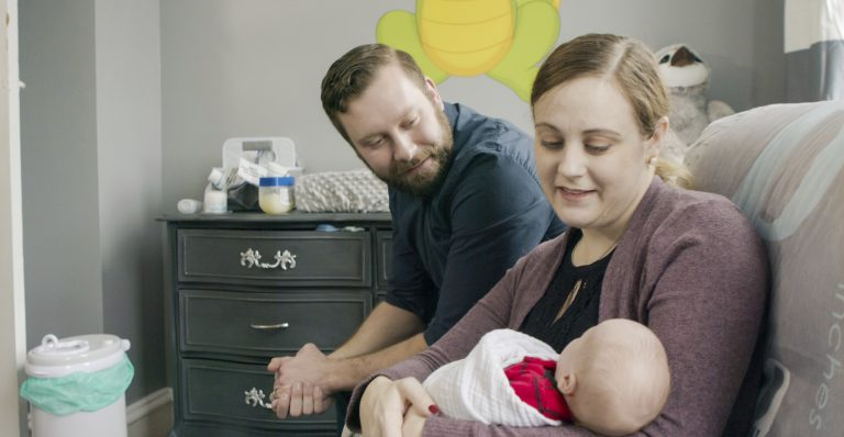 Jennifer and Drew Gobrecht look at their baby, Benjamin, at home in Ridley Park, Pa. Jennifer gave birth in November 2019 following a uterine transplant. (Penn Medicine via AP)