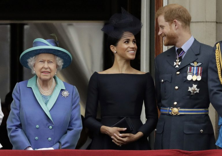 In this Tuesday, July 10, 2018 file photo Britain's Queen Elizabeth II, and Meghan the Duchess of Sussex and Prince Harry watch a flypast of Royal Air Force aircraft pass over Buckingham Palace in London. (Matt Dunham/AP Photo)