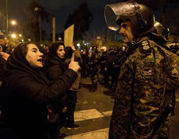 A woman attending a candlelight vigil to remember the victims of the Ukraine plane crash, talks to a policeman, at the gate of Amri Kabir University in Tehran, Iran.  (Mona Hoobehfekr/ISNA via AP)
