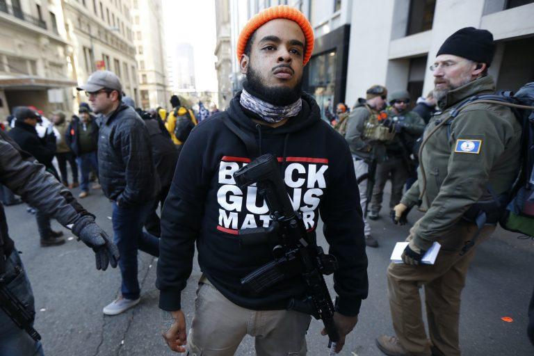 A man walks in the crowd during a pro-gun rally, Monday, Jan. 20, 2020, in Richmond, Va. (Julio Cortez/AP Photo)