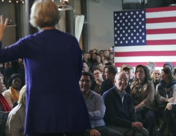 In this Jan. 10, 2020, file photo, Bruce Mann, husband of Democratic presidential candidate Sen. Elizabeth Warren, D-Mass., right, smiles as he listens to his wife during a campaign stop in Dover, N.H. (Charles Krupa/AP Photo)