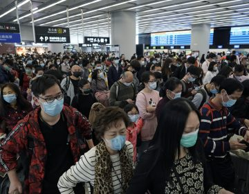 In this Thursday, Jan. 23, 2020 file photo, Passengers wear protective face masks at the departure hall of the high speed train station in Hong Kong. (Kin Cheung/AP Photo)