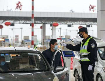 In this Jan. 23, 2020, file photo, a policeman uses a digital thermometer to take a driver's temperature at a checkpoint at a highway toll gate in Wuhan in central China's Hubei Province. Cutting off access to entire cities with millions of residents to stop a new virus outbreak is a step few countries other than China would consider, but it is made possible by the ruling Communist Party's extensive social controls and experience fighting the 2002-03 outbreak of SARS. (Chinatopix via AP)