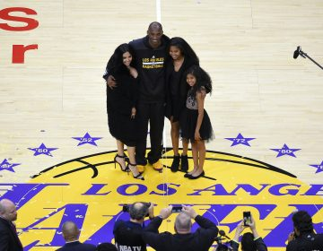 In this April 13, 2016, file photo, Los Angeles Lakers' Kobe Bryant poses for pictures with his wife Vanessa, left, and daughters Natalia, second from right, and Gianna as they stand on the court after an NBA basketball game against the Utah Jazz, in Los Angeles. (Mark J. Terrill/AP Photo)