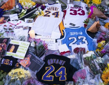 Flowers, jerseys and imagery is left in remembrance to Kobe Bryant at a small memorial at the entrance of the Bryant Gymnasium at Lower Merion High School, Monday, Jan. 27, 2020, in Wynnewood, PA. Bryant, the 18-time NBA All-Star who won five championships and became one of the greatest basketball players of his generation during a 20-year career with the Los Angeles Lakers, died in a helicopter crash Sunday, Jan. 26, 2020. (AP Photo/Chris Szagola)