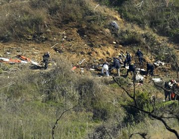 Investigators work the scene of a helicopter crash that killed former NBA basketball player Kobe Bryant, his 13-year-old daughter, Gianna, and seven others Monday, Jan. 27, 2020, in Calabasas, Calif. (Mark J. Terrill/AP Photo)