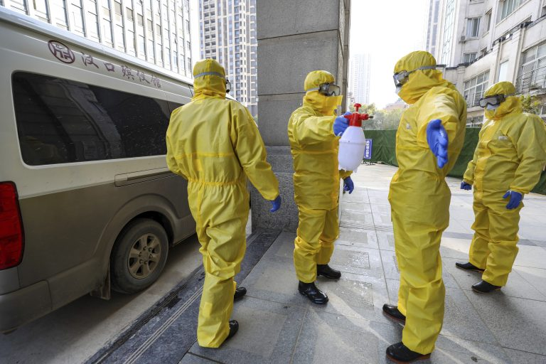 Funeral workers disinfect themselves after handling a virus victim in Wuhan in central China's Hubei Province, Thursday, Jan. 30, 2020. China counted 170 deaths from a new virus Thursday and more countries reported infections, including some spread locally, as foreign evacuees from China's worst-hit region returned home to medical observation and even isolation. (Chinatopix via AP)