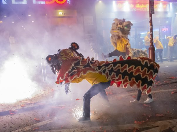 Lion dancers from the Philadelphia Suns perform in front of businesses on North 10th Street. (Jonathan Wilson for WHYY)