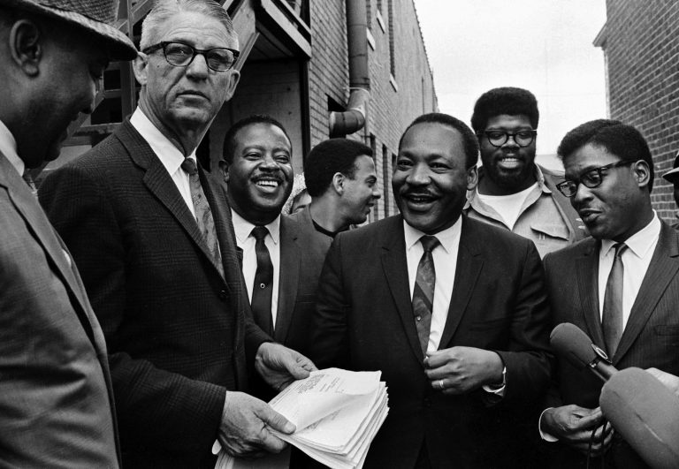 Dr. Martin Luther King Jr., center, and Rev. Ralph Abernathy, third from left, share a laugh outside  court in Decatur, Ga., Oct. 25, 1960. Others are unidentified. Andrew Young is seen at center, facing right. (AP Photo)