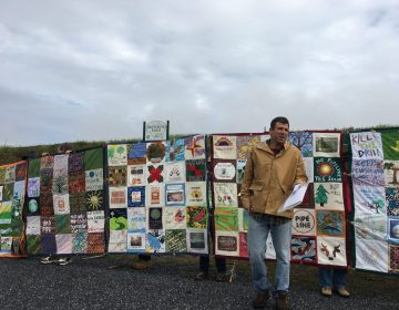 Mark Clatterbuck stands in front of a quilt designed to protest the Atlantic Sunrise pipeline. (Marie Cusick/StateImpact Pennsylvania)