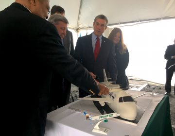 Instead of cutting a ribbon, Gov. John Carney joined leaders from the Delaware River and Bay Authority to cut a cake marking the return of commercial passenger flights to Delaware via Frontier Airlines. (Mark Eichmann/WHYY)