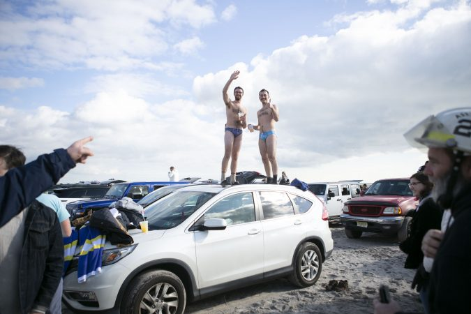 Pete Stanfer, left, and William Dean dance on top of their car during the 2020 polar bear plunge in Margate, NJ on Wednesday, January 1, 2020. (Miguel Martinez for WHYY)
