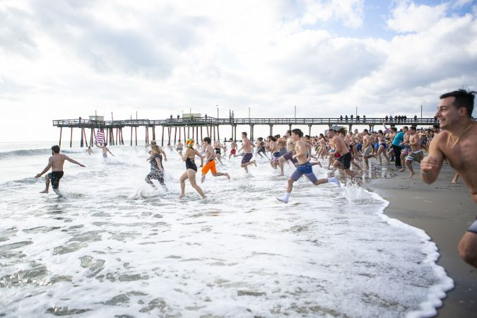 Participants of the 2020 polar bear plunge in Margate, NJ  run to the ocean on Wednesday, January 1, 2020. (Miguel Martinez for WHYY)